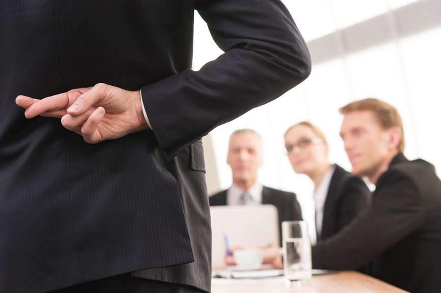 Lying? Rear view of man in formalwear keeping fingers crossed behind his back while three people sitting on background